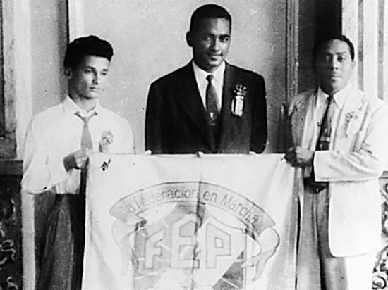 """Foto tomada en el Congreso de Estudiantes del 12 de diciembre de 1957, en el Aula Máxima del Instituto Nacional de Panamá: Floyd Britton Morrison (en el centro), Presidente del Congreso; Polidoro Pinzón Castrellón (a la izquierda), Vice-Presidente del Congreso y Andrés Cantillo Murillo (a la derecha), Secretario General de la Federación de Estudiantes de Panamá F.E.P. Se puede observar el escudo de la desaparecida Federación de Estudiantes de Panamá F.E.P. y su lema: """"La Federación en Marcha."""""""