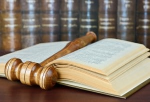 Wood gavel and old yellowed book on the background of shelves of old books